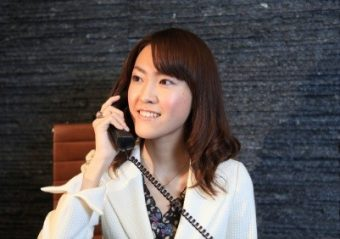 Young Woman receiving calls at reception. dark sparkly granite stone background.
