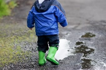 A boy about to play in a puddle.