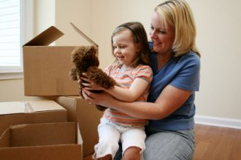 A woman and child unpack boxes in a new home