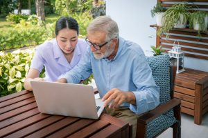 Carer assisting elderly service user to develop digital skills